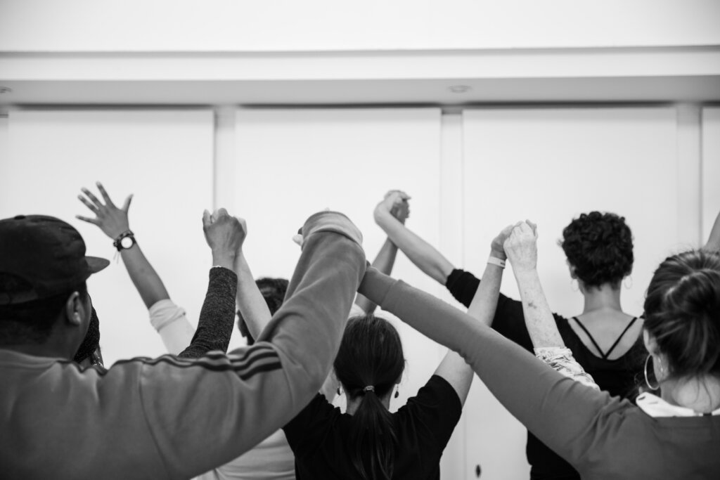 Black and white image of a group of women holding hands in the air